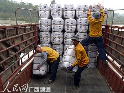 图为铁路装卸工人把汽车上的救灾棉被搬到火车上(黄彩辉/摄)