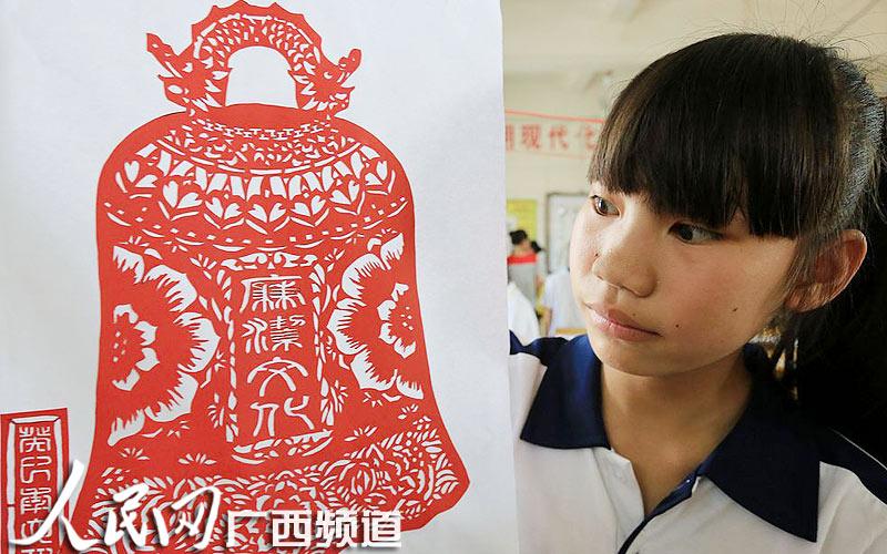 日本 袜子/6月20日,在融安县初级中学校园,一名学生在观看剪纸作品。(...