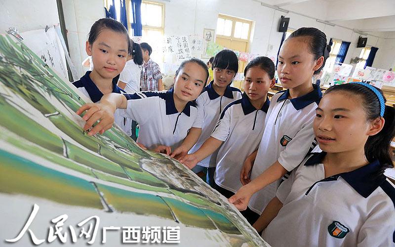 作品 融安县/6月20日,学生们在融安县初级中学校园观看展出的廉政文化作品...