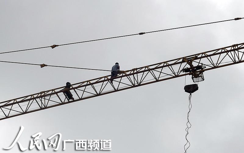 工地机械台吊臂上的男子 -广西一工地男子40米高空悬坐讨赔偿