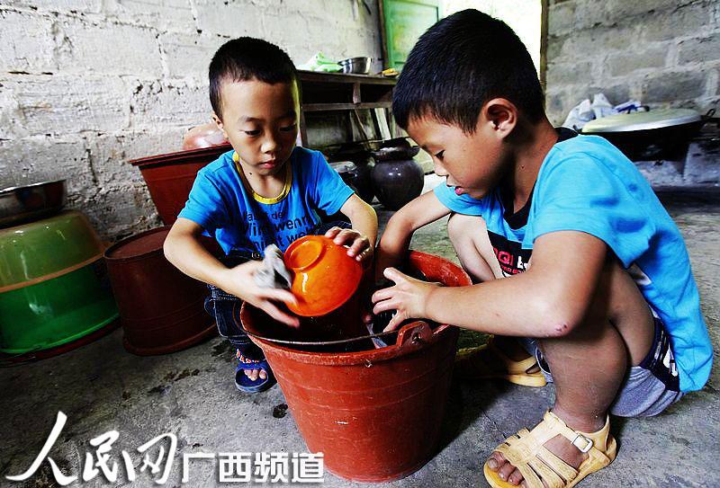 两名小朋友在厨房里帮老师洗碗