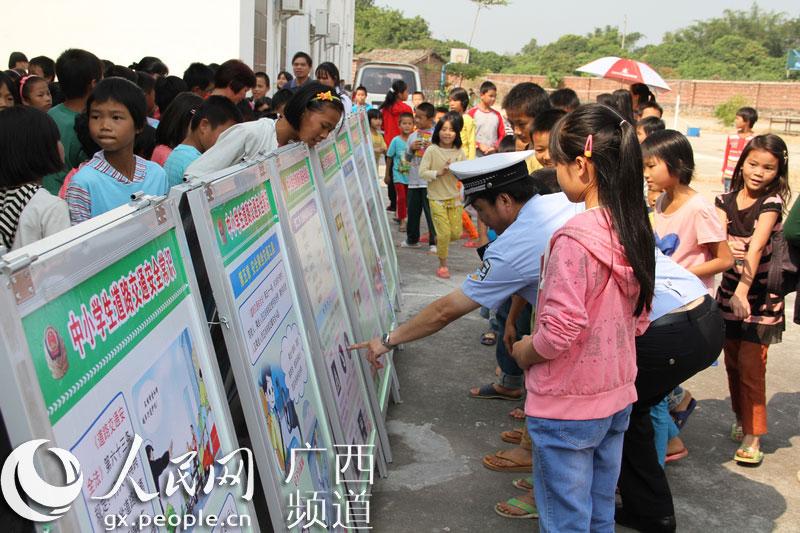 桂平交警在交通安全展板前向小学生讲解文明交通知识