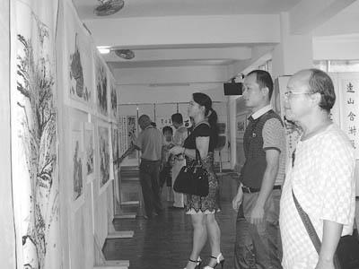 10月1日,书画爱好者在观看展出的书法、美术作品.国庆节期