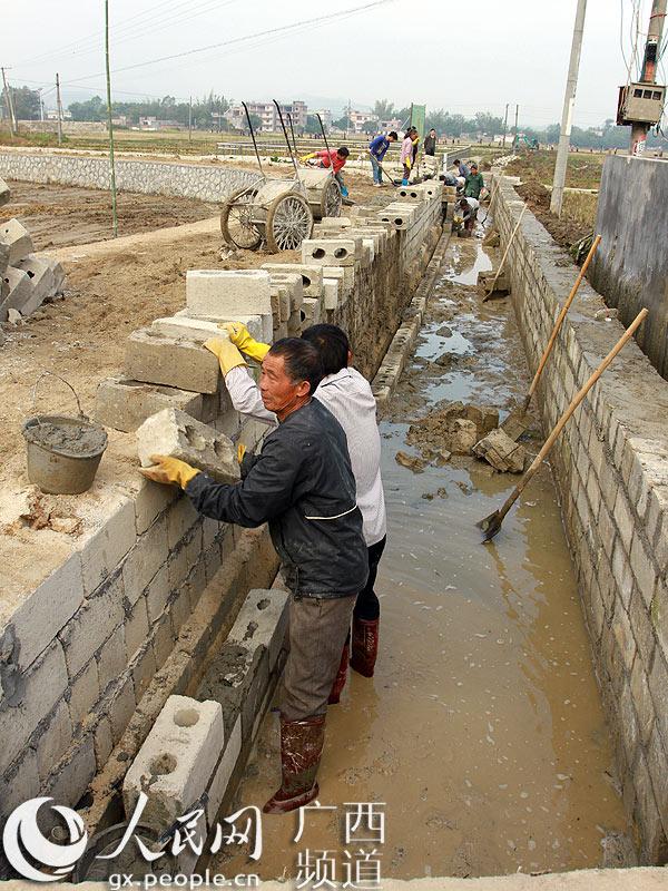 图为工人在搬砖砌墙