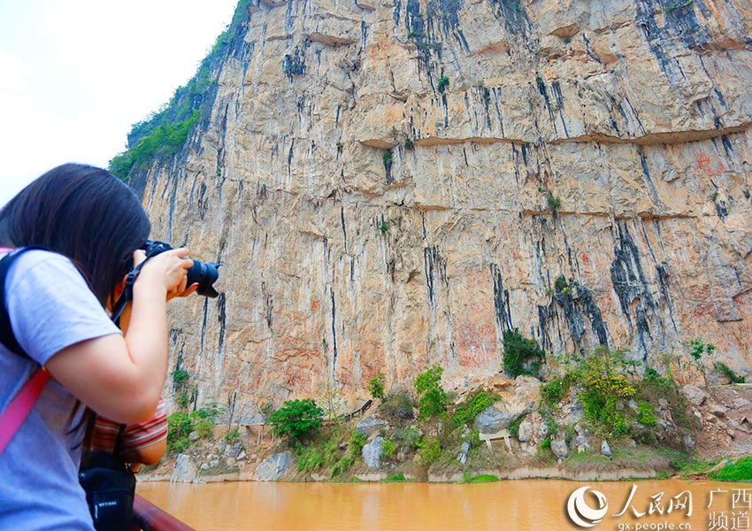 """记者在左江上拍摄花山岩画,对面陡峭石壁上的红色区域即为大片的""""蹲式人形"""""""