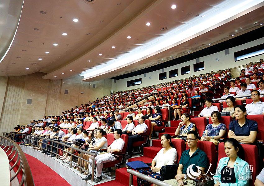 观众专注听着台上嘉宾讲诉关于莫振高的先进事迹