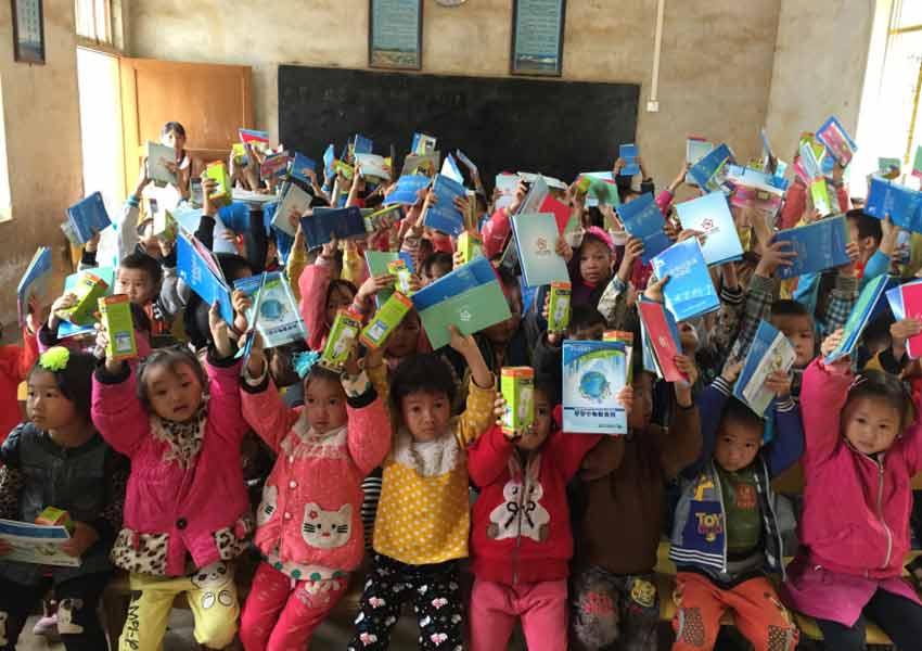 拿到学习文具,可爱的孩子们欢呼着.