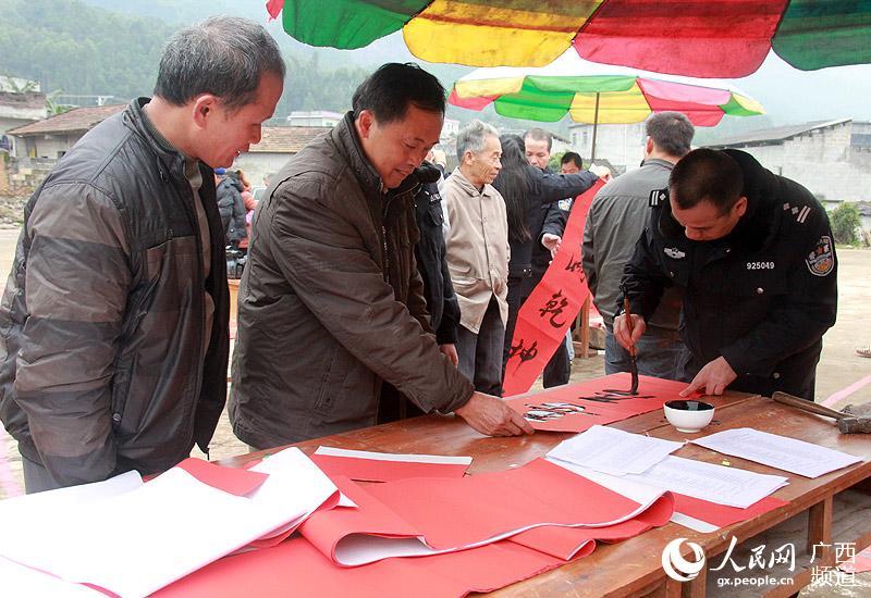 村民在挑选春联让书法家帮忙书写