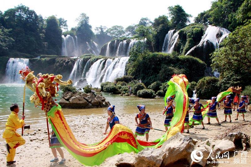 4月7日,在广西大新县德天瀑布景区里,群众正在进行舞龙表演.