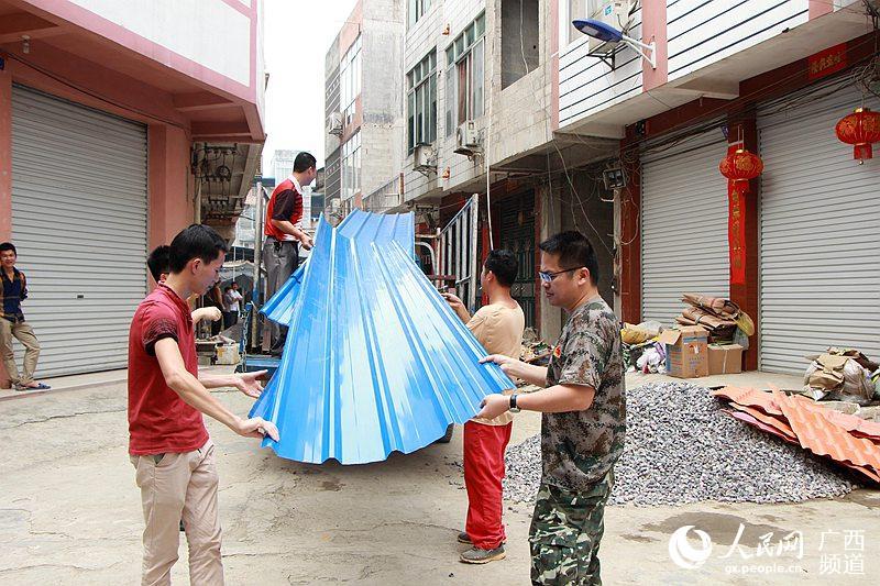 4月13日,广西大新县桃城镇新城社区,该镇领导干部正在把镇政府为贫困