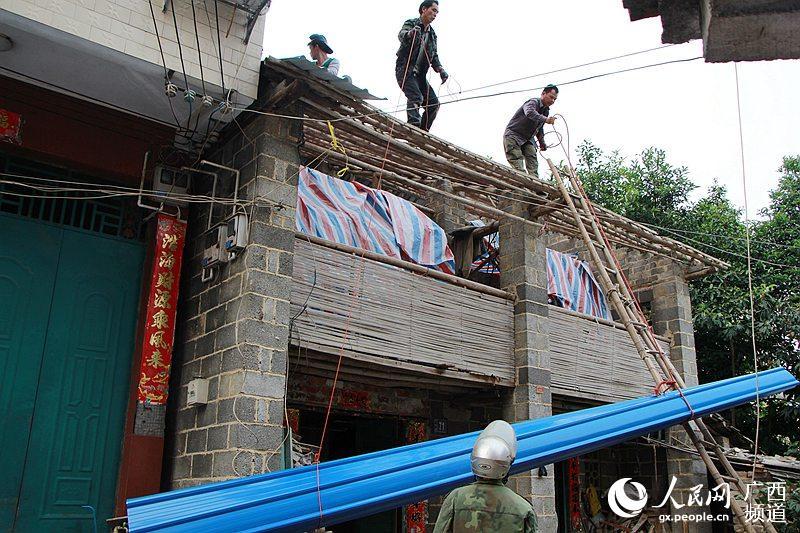 4月13日,广西大新县桃城镇新城社区,工人正把该镇政府为贫困户购买的