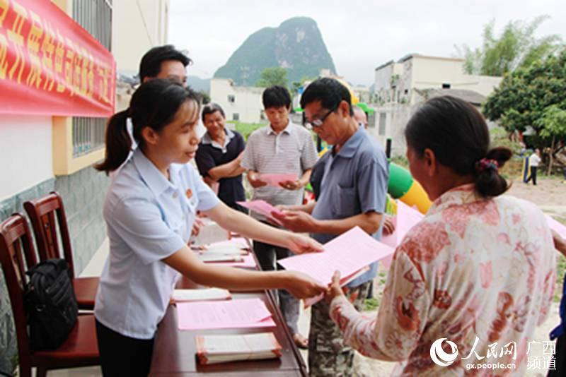 5月13日,在广西大新县桃城镇万礼村教礼屯,该县法院工作人员正在向