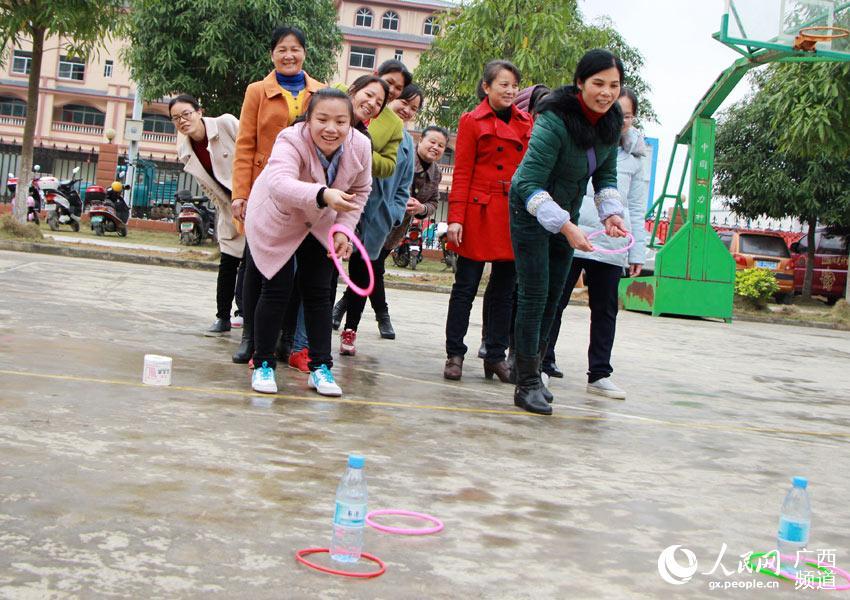 3月7日,在广西大新县桃城镇政府大院,妇女干部正在玩抛圈圈游戏.