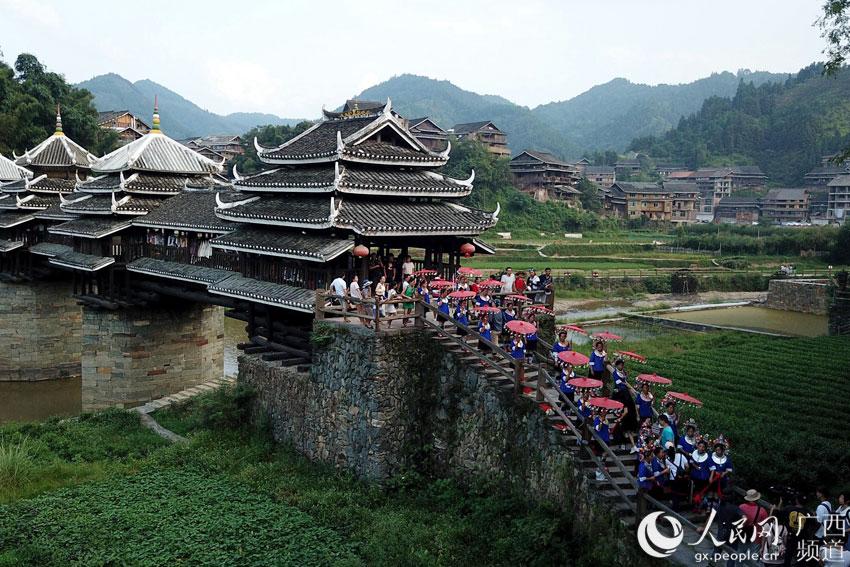 10月3日,在三江侗族自治县林溪镇程阳风雨桥头,人们在欢唱拦路歌
