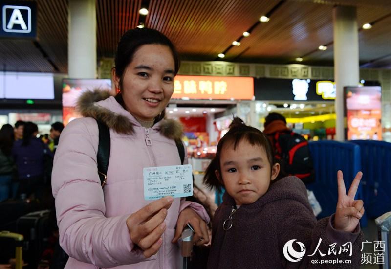 图为广西百色籍在粤务工贫困户拿着免费车片准备进站上车(韦克家 摄)