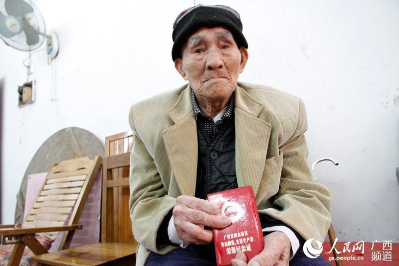 """韦兆良老人向人们展示""""劳模""""荣誉纪念证书"""