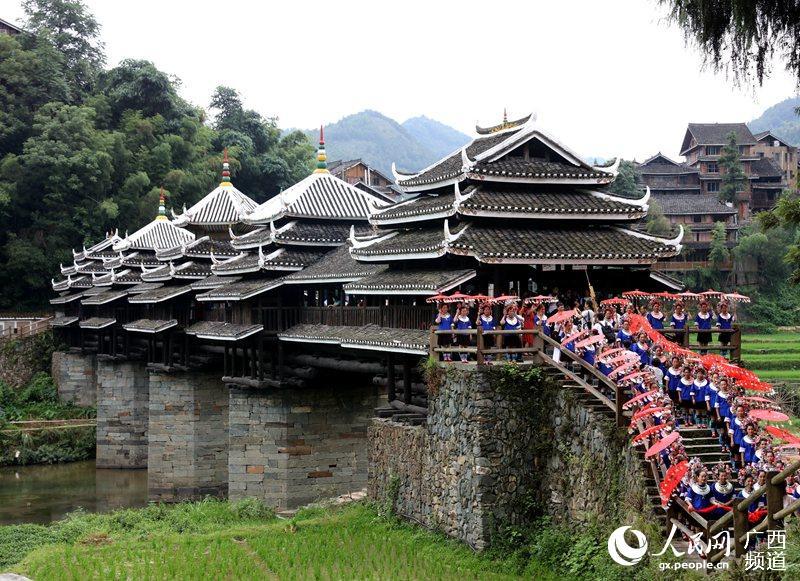 7月4日,村民在广西柳州三江侗族自治县林溪镇程阳风雨桥头拦路迎宾