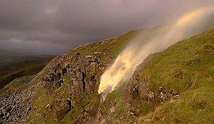 暴风致使山顶瀑布倒流 阳光照射挂起彩虹