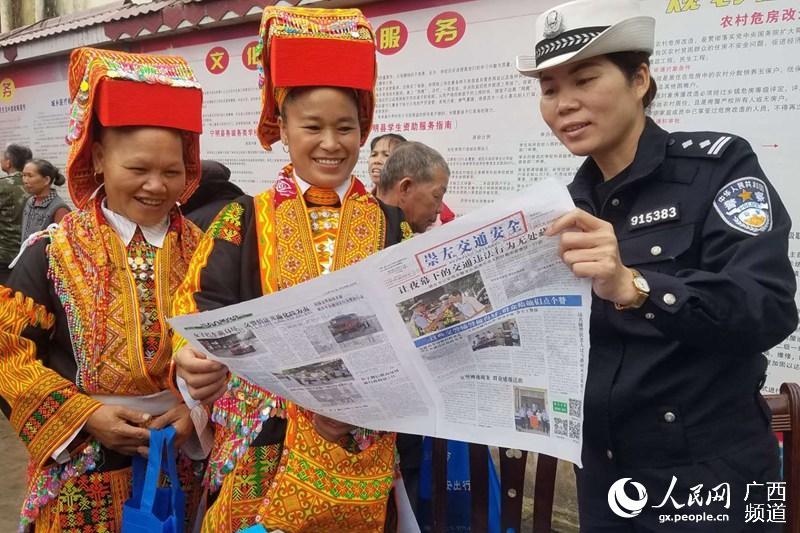 4月16日,广西壮族自治区宁明县公安局交警大队民警在地处边境一线的爱店镇堪爱村壮族歌坡节活动中向瑶族妇女宣传交通安全知识