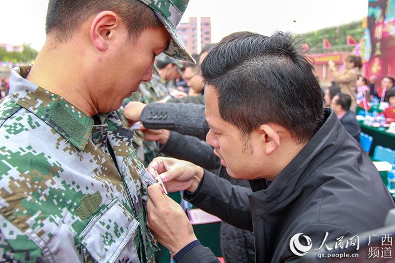 领导嘉宾为新生佩戴校徽(吴明江 摄)