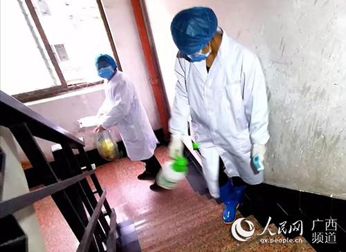 工作人员给杨大姐家楼梯消毒。张相兵摄
