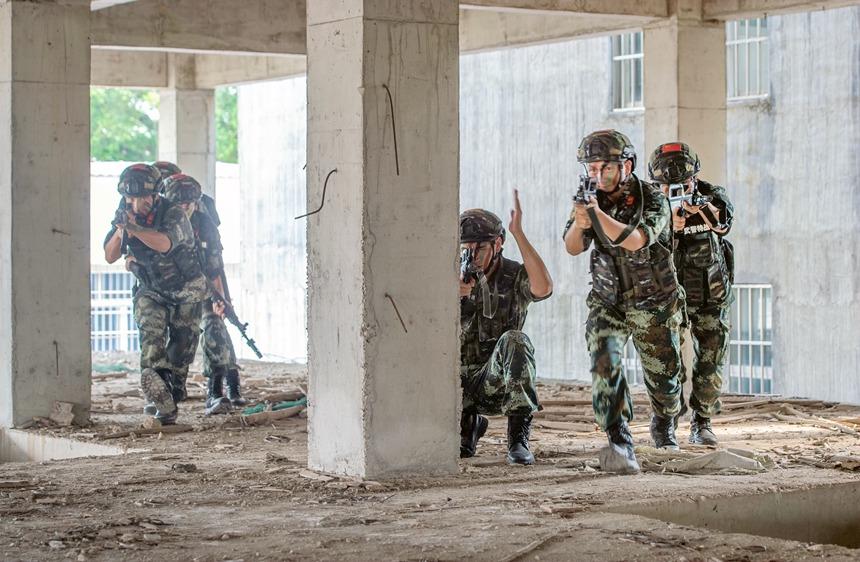 一名武警官兵示意队友发起突击。