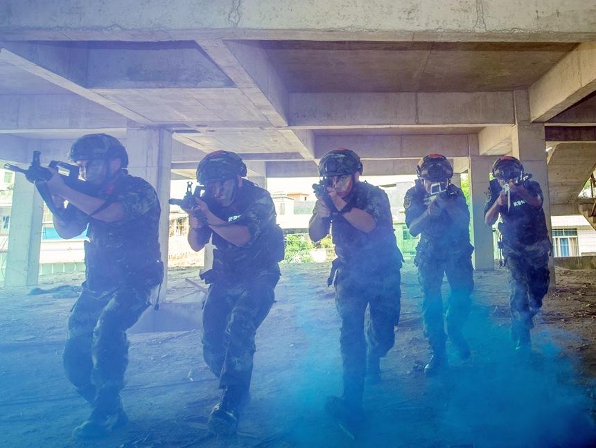 武警官兵以战术队形在楼房内搜索前进。