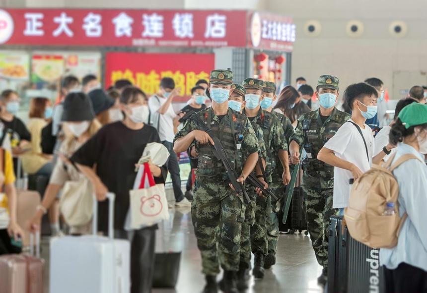 武警官兵在高铁站内徒步武装巡逻。