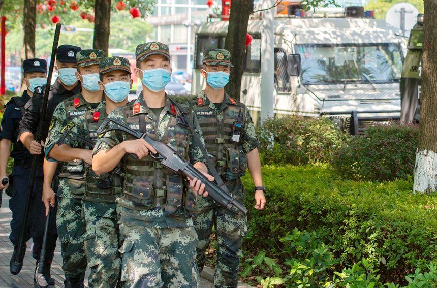 武警官兵与特警在广场徒步巡逻。