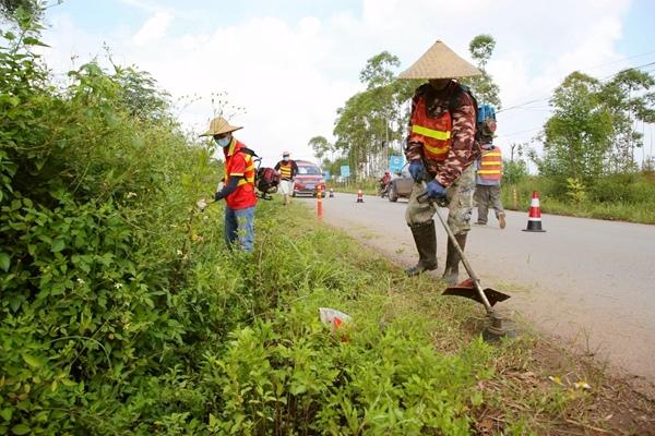 公路养护工作人员在清除公路杂草。刘志宁摄