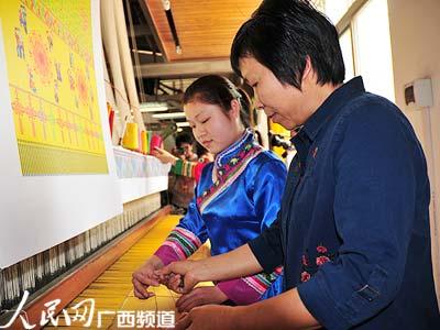 从事壮锦织造近40年的中国织锦工艺大师、广西非物质文化遗产传承人谭湘光正向22岁的卓利荣传授技艺,她俩将和另外3名女工一同织造世界上最大的壮锦,献给2010上海世博会。