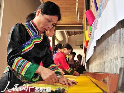 今年38岁的朱小琼正与4名女工一同为2010上海世博会织造世界上最大的壮锦。壮锦织成后,将于今年8月举行的2010上海世博会广西活动周上赠出。